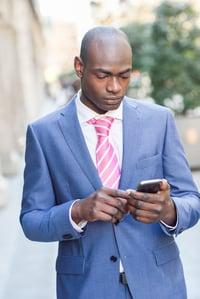 black-businessman-reading-his-smartphone-in-urban--FS8T5CH