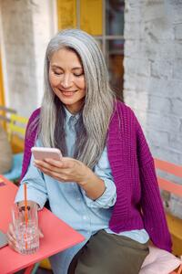 pretty-senior-asian-lady-reads-sms-on-mobile-phone-AGXLJZM