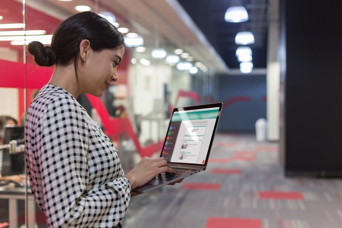 Standing woman creating an employee newsletter on a laptop