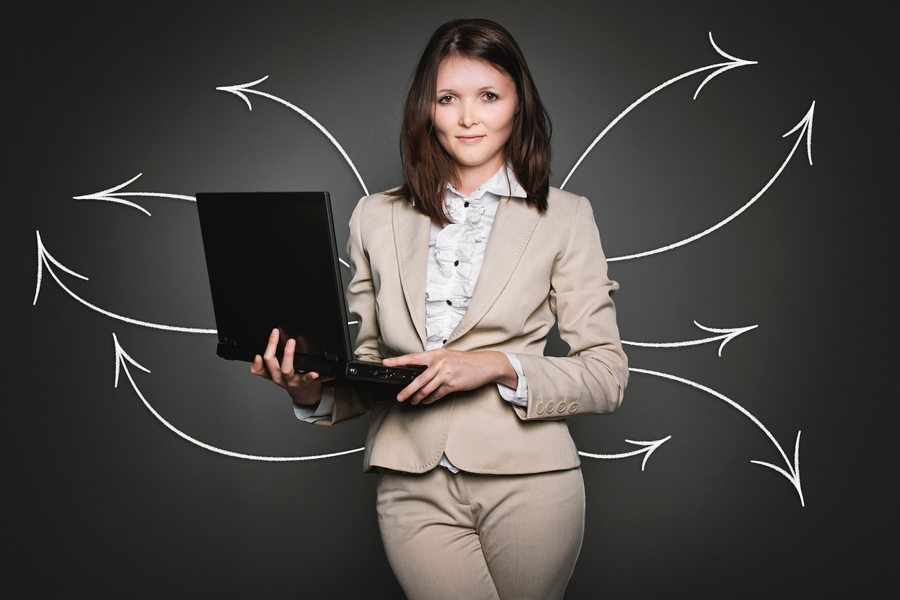 Woman standing in front of a blackboard and holding a laptop.